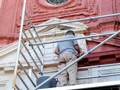 Denkmalpflege, Restaurierung. Mann auf Gerüst restauriert Fassade einer Kirche.