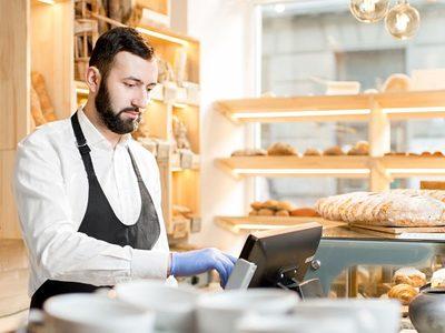 Bäckerei-Verkäufer gibt Geldbetrag in Kassensystem ein.