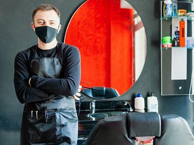 Friseur in seinem Salon mit Maske