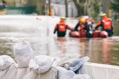 Rettungskräfte mit Rettungsboot beim Hochwasser-Einsatz. Im Vordergrund Sandsäche.